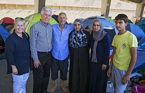 President Uchtdorf and his daughter visiting refugees